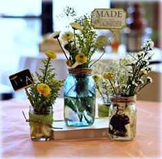 A mixture of small and large ball jars with pictures inside and twine at the top.  Not these flower arrangements.