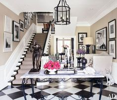 An entrance hall featuring a black and white painted wood floor | archdigest.com
