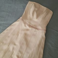 "B2 dress Beautiful light pink strapless dress. Corset fitted top. Zipper and hook in back. Only worn once. New Condition. The last photo shows a small line in the fabric. There are two of these but they aren't very noticible. Size 10 but it's a small 10. Fits more like an 8. 80"" top to bottom. Color most accurate in first photo. Dry clean. B2 Dresses"