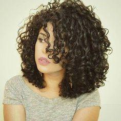 medium layered curly hair with long bangs