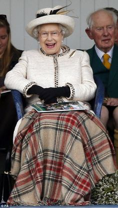 She wore a cream jacket, matching hat and placed a tartan rug over her lap...
