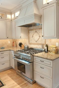 granite new venetian gold white cabinets stainless steel gas oven wood flooring