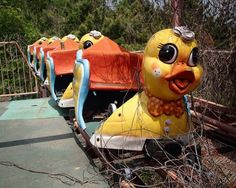 carousel horse in front of rusty rollercoaster rails