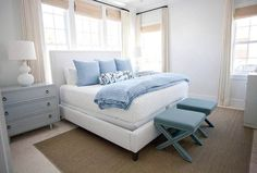 White and blue cottage bedroom features a white upholstered bed dressed in white and blue bedding sits in front of a row of windows dressed in tan roman shade layered with tan curtains. White Bedroom Set, White Bedroom Furniture, Blue Bedroom, Bedroom Decor, Bedroom Ideas, House Furniture, Kitchen Furniture, Bed Under Windows, Front Windows