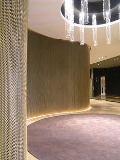 Wire mesh curtains in brass. Full feature wall at Condor Towers, Hilton Adelaide. Architect: Hassell
