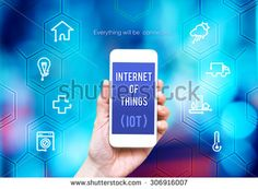 Hand holding smart phone with Internet of things (IoT) word and object icon and blue blur background, Digital business concept.