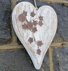 Rustic wooden heart with metal flowers.