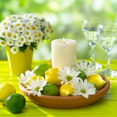Create a table center piece with lemons, limes, daisies and a candle. Description from pinterest.com. I searched for this on bing.com/images