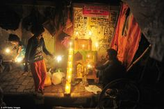Children play with sparklers in a street adorned with candles and shrines in Allahbad, Ind...