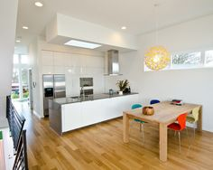 A sunny and cheery pendant painted yellow on the inside with pop of color chairs in this white minimalist kitchen