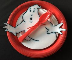 """Ghostbusters Birthday Party place setting with plates from Party City. Red Plastic Dinner Plates measuring 10 1/4"""" in diameter and White Premium Plastic Dessert Plates measuring 7 1/2"""" in diameter. The ghost is about 8.375"""" tall."""