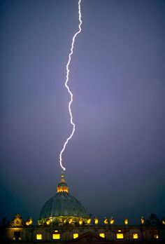 "Lightning strikes St Peter's dome at the Vatican on February 11, 2013. ""Hours after Pope Benedict XVI stunned the world by announcing he would resign at the end of the month, a blinding shaft of lightning shot down from the heavens and struck the rod atop the white cross on St. Peter's Basilica at the Vatican.AFP photographer Filippo Monteforte – his camera already trained on the Basilica's cupola – pushed the button that yielded the image."""