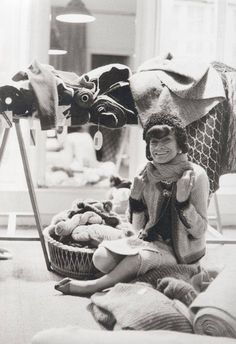 Coco Chanel sorrounded by tweeds and wools textiles in her atelier