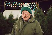 An elderly man posing with a christmas tree on his lot by Stalman & Boniecka - Stocksy United - Royalty-Free Stock Photos