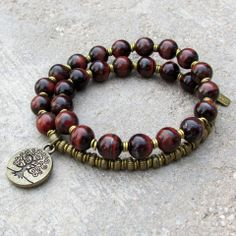 27 bead mala bracelet, made with rich genuine red tiger's eye gemstones, hand made African Trade Beads and a Tree of life charm. It wraps as a bracelet, (stringed on thick hi-tec elastic). Great on me