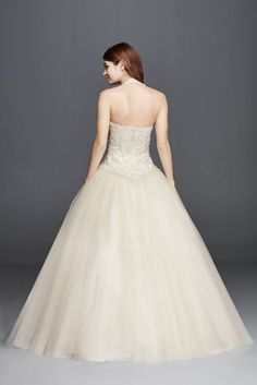 Make your grand entrance and channel royal appeal in this tulle halter wedding dress. Featuring a basque waist, beaded…
