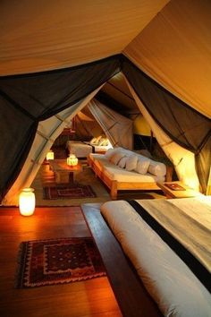Like this! Have a windowless short attic? Make into a divine year-round camp. Just attach large sheet from center of ceiling to top of wall then to bottom of wall. Separate spaces with a contrasting hued see through sheet attached from ceiling and wall. Tie back with strap. Repeat using a canvas. Light the room with warm hued, floor placed lamps. Use low furniture like platform beds.
