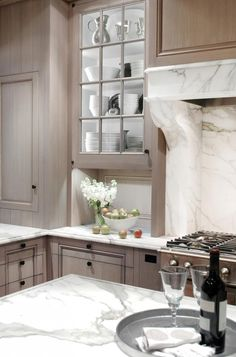 Faded light wooden cabins and marble counter tops is a very chic and elegant look.