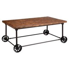 Industrial-style coffee table with a metal base and wheel feet.    Product: Coffee tableConstruction Material: Wood veneer and metalColor: Antique brownFeatures: Metal industrial castersDimensions: 19 H x 46 W x 28 D