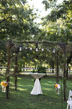 Arbor decorated with mason jars, ivy, & branches. Simply Gorgeous.- Venue at the Grove