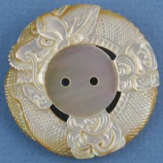 Carved shell button with dragon design.