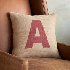 "Rough and tumble burlap pillows, each emblazoned with the letter of your choice, spell out a name, a word or your initials. Hand loomed jute burlap zippered cover with duck feather/down insert. Imported. Exclusive. 18"" SQ."