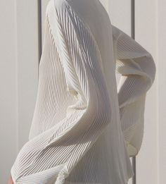 Simple and dynamic. A cream micro pleated blouse featuring bell shaped sleeves. Shop at www.michaela.co ~ #michaelaco