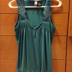 Adorable teal tank with lace detailing This gorgeous tank has detailing galore with detailing on straps and buttons on the vneck. It has a gathered bottom that hugs your frame. Preloved but no wear or tear. Sorry no trades Love on a Hanger Tops Tank Tops