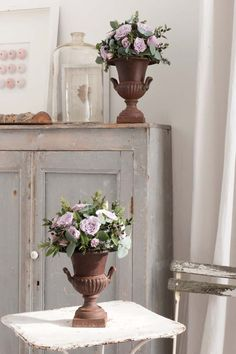 Antique urns containing 'Silver Surfer' spray roses, fresh flowering rosemary, sage and mixed foliage, arranged to order by Scarlet Feather Florist.