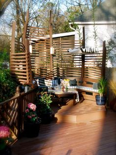 A unique way to provide shade and an interesting structural backdrop to a back deck is to add vertical wooden planks. In varying — but balanced — levels, the spaced planks provide the perfect amount of shade from every direction. Built-in bench seating on a raised deck platform sets the entire seating area apart from the remainder of the deck.