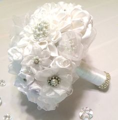 Bouquet is made up of white handmade satin ribbon and organza flowers each with their own glass pearl and rhinestone brooch. The handle is wrapped in white satin ribbon and adorned with elegant pearl and rhinestone ribbon. Medium size pictured