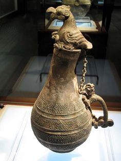 Gourd-shaped Vessel, Spring And Autumn period, 770-476 BC, Shanxi Museum.  A bird rests atop the bent neck of the vessel. A chain extends down to its zoomorph handle. The bulbous body of the vase is decorated in four bands of closely-set pimples. Compare: a similar vessel from Xi'an.