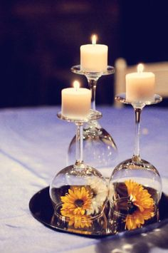 Simple Centerpieces - overturned wine glasses with flowers, mirror, and votive candles.