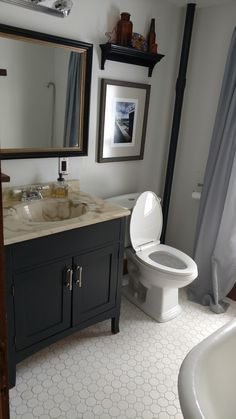 Classic bathroom update with octagon dot white tile and Madison Montpellier White by Valspar paint. Vanity is Dark Kettle Black by Valspar.