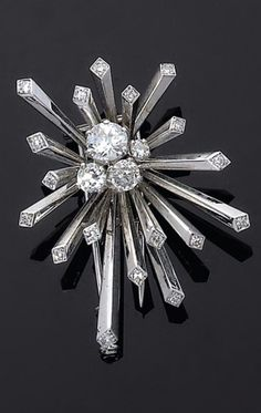 """Mauboussin . 1935. Clip """"Fireworks"""", Set in the center with diamonds of four different sizes . The rays are each terminated with a round diamond . Mounting in platinum and gold gris. Signéd Mauboussin on mount."""