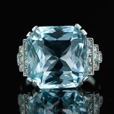 An original Aquamarine ring from the 1930's. A beautiful pale greenish blue 20.00 carat Aquamarine is set in platinum with split prongs and flanked by diamond set shoulders that step down and are finished with milgrain details.