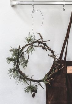Create a simple Christmas wreath with a spruce branch with small cones.