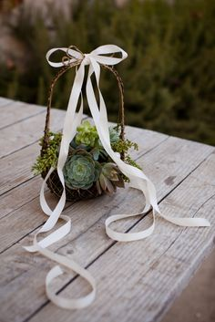 The flower girl will carry a petite basket covered in moss with scattered purple and green succulents, with ivory rose petals for tossing.  And a white ribbon accent will be used to tie the rings.