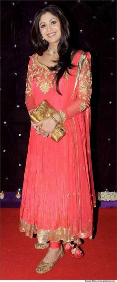 Shilpa Shetty in a vibrant pink designer salwar kameez with heavy gold embroidery on the neckline and full-length sleeves