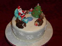 - I made this Christmas cake for my family.  I'm new to making fondant figures, so these took me awhile.  Santa is enjoying his cookie while the reindeer are opening their gifts (see Rudolph got a mini Rudolph for Christmas).  The cake was chocolate with peppermint buttercream and crushed candy canes.  The outside was dusted with sanding sugar and decorated with royal icing snowflakes.  I got lots of tips from the discussion and other people's cakes on CC - thank you!