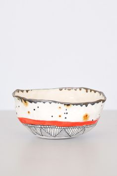 Hand-pinched bowl with red stripe from Brooklyn artist Suzanne Sullivan. Due to their handmade nature, each bowl is different in pattern and size. Use to hold jewelry, small items or for kitchen servi