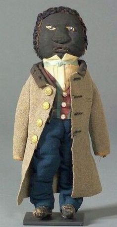 Folk Art Doll, America, c. 1863, hand-sewn figure of a black gentleman, with stuffed black woven wool fabric head and body, the face with applied stuffed nose and mouth and glass button eyes, leather hands and boots; he is dressed in hand-sewn garments made of wool and cotton textiles, including a grey wool frock coat with velvet collar and brass eagle buttons, a black wool morning coat, wool plaid vest, blue wool trousers, and white cotton shirt, ht. 15 1/2 in.