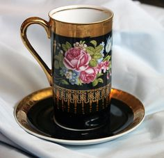 Tall porcelain cup and saucer.  Royal Crown Arnart-Dansant. Hand painted roses and gold pattern on black background.