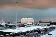 A Dramatic Sky and the Lord Warden House under Snow, Dover Harbour, Kent, England, UK. Built as the Lord Warden Hotel in the Western Docks by Victorian architect Samuel Beazley between 1848-1853. Became Royal Navy's HMS Wasp Shore Station during Second World War. Now Lord Warden House and offices of freight agents. Grade II Listed Building. Winter view (January 2013) from A20 Limekiln Street railway bridge. Architecture, World War II, and History. See: http://www.panoramio.com/photo/85090190