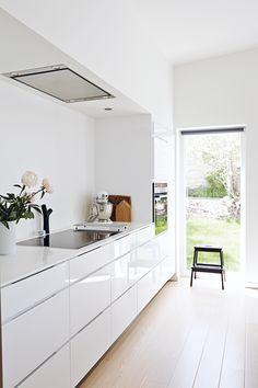 Strakke witte keuken met kooknis en halfhoge keukenkasten..