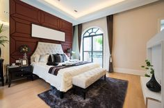 A quilted headboard rests against a rich wood wall. Light hardwood floors complement the beige walls.
