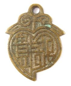 """Peach charm reverse sideThis is the reverse side of the charm.The two Chinese characters are again written in a very stylized seal script. The characters are read right to left as fu gui (富贵) meaning """"wealth and rank"""".The charm is 45 mm in length and 35 mm in width.The weight is 17.7 grams."""