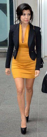 Kourtney Kardashian in a fitted yellow dress and black blazer