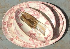 helmiäiskädensijaiset jälkiruokahaarukat ja -veitset punakuvioisilla ruoka- ja tarjoilulautasilla . veitset ja haarukat 20 luvulta Ranskasta . 6 kpl . lautaset 1900 luvun alusta Ranskasta . @kooPernu