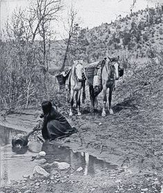 Apache women were skilled basket makers. Edward Curtis took this 1903 photograph of a woman filling her watertight basket with water to take back to camp. – Courtesy Library of Congress –